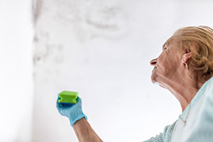 Woman cleaning up mold after a leaking roof.