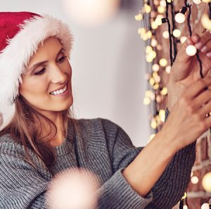 Woman in a Santa hat hanging holiday lights safely