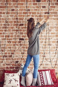 Woman hanging lights using holiday lighting safety precautions